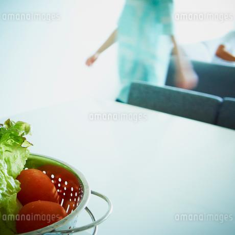 水切りボウルに入った野菜と歩く女性の写真素材 [FYI02048644]