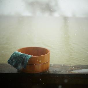 雪降る露天風呂の風呂桶と手ぬぐいの写真素材 [FYI02048669]