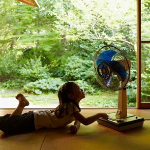 扇風機の前に寝転ぶ女の子の写真素材 [FYI02048701]