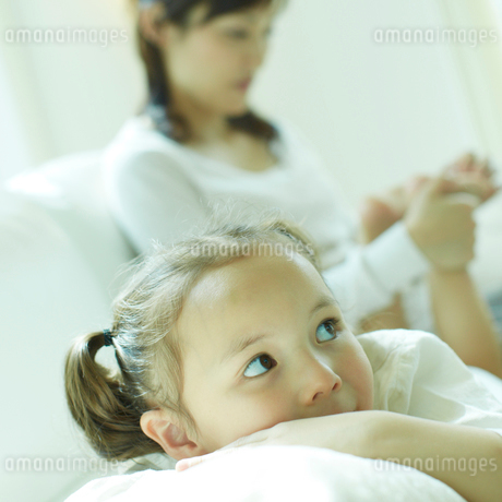 リラックスする女の子と足をマッサージする母親の写真素材 [FYI02048782]