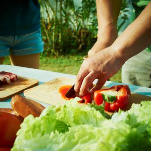 バーベキューの野菜を切る男性の手元の写真素材 [FYI02048875]