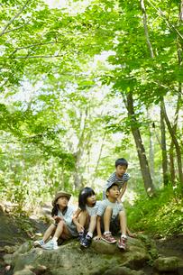 森林の岩の上に座る4人の子供達の写真素材 [FYI02048975]