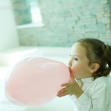 風船を膨らませる女の子の写真素材 [FYI02049115]
