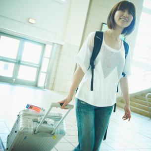 スーツケースを持って歩く女性の写真素材 [FYI02049130]