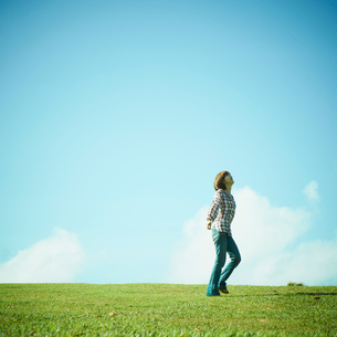 芝生の上に立つ女性と青空の写真素材 [FYI02049164]
