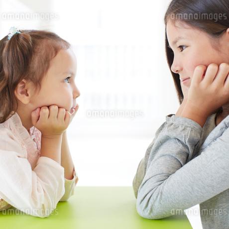 頬杖をつき見つめ合う2人の女の子の写真素材 [FYI02049189]