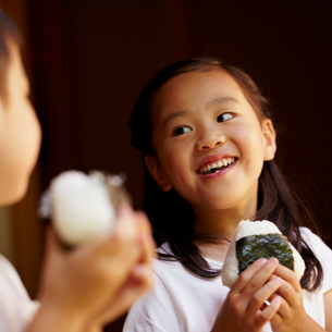 おにぎりを食べる女の子と男の子の写真素材 [FYI02049255]
