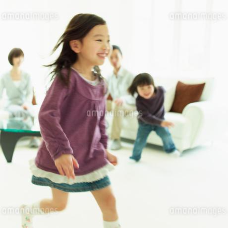 リビングルームを走る女の子とソファに座るファミリーの写真素材 [FYI02049345]