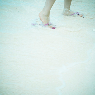 波打ち際を歩く女性の足元の写真素材 [FYI02049430]