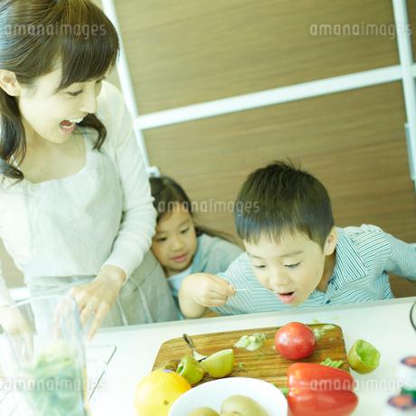 キッチンでつまみ食いをする男の子と母親と女の子の写真素材 [FYI02049556]