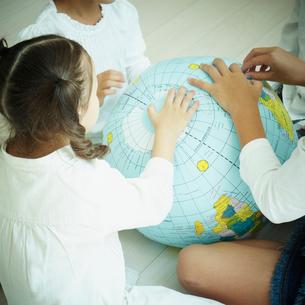 地球儀のボールに触れる子供達の写真素材 [FYI02049572]