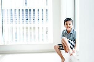 窓辺に座る男の子の写真素材 [FYI02049631]