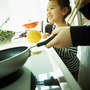 キッチンに立つ女の子と料理をする母親の手元の写真素材 [FYI02049669]