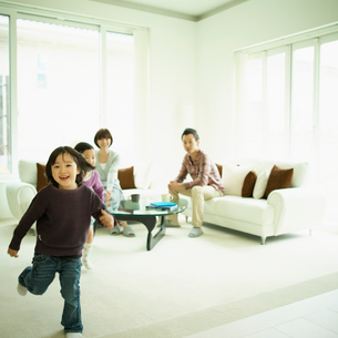 リビングルームを走る男の子とソファに座るファミリーの写真素材 [FYI02049872]