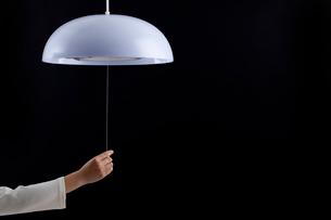 照明のスイッチひもを持つ手の写真素材 [FYI02049936]