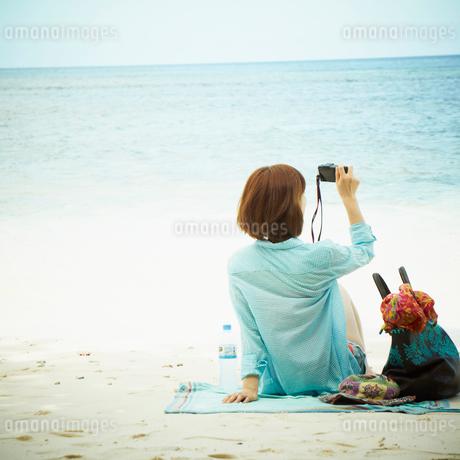 砂浜に座りカメラを構える女性の写真素材 [FYI02049975]