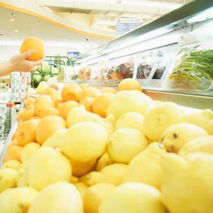 スーパーでオレンジを持つ女性の手元の写真素材 [FYI02049987]