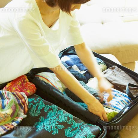 スーツケースに荷物を詰める女性の写真素材 [FYI02049989]