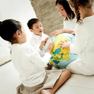地球儀のボールを囲む子供達の写真素材 [FYI02049995]