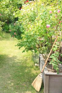 花咲く新緑の庭とたて掛けたほうきの写真素材 [FYI02050025]