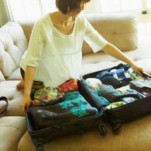 スーツケースに荷物を詰める女性の写真素材 [FYI02050190]