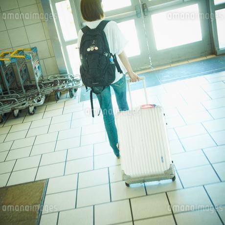 スーツケースを持って歩く女性の写真素材 [FYI02050230]