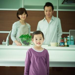 笑顔の女の子とキッチンから見守る両親の写真素材 [FYI02050315]