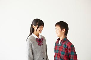 笑顔で向かい合う男の子と女子学生の写真素材 [FYI02050389]