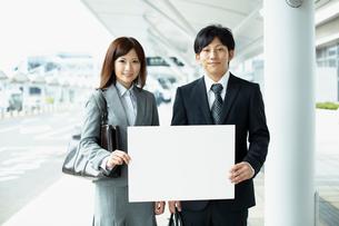 メッセージボードを持つビジネスマンとビジネスウーマンの写真素材 [FYI02050430]
