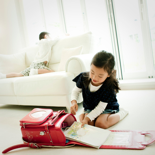 ランドセルに教科書を入れる女の子の写真素材 [FYI02050443]
