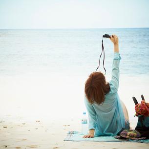 砂浜に座りカメラを構える女性の写真素材 [FYI02050484]