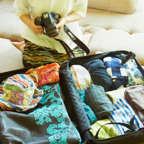 スーツケースの前でカメラを持つ女性の写真素材 [FYI02050703]