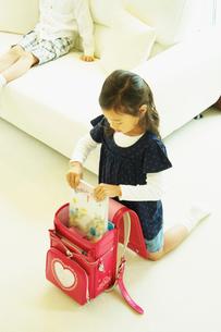 ランドセルに教科書を入れる女の子の写真素材 [FYI02050795]