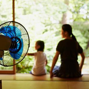 扇風機と縁側に座る親子の写真素材 [FYI02050796]
