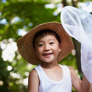 補虫網を持ち麦わら帽子を被った男の子の写真素材 [FYI02050860]