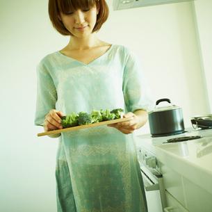 切ったブロッコリーを運ぶ女性の写真素材 [FYI02051104]