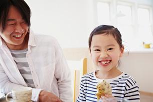 パンを食べる女の子と笑顔の父親の写真素材 [FYI02051133]