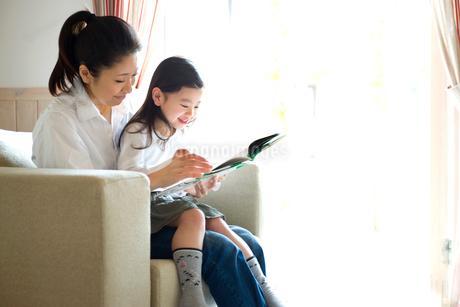 絵本を読む母親と娘の写真素材 [FYI02051160]