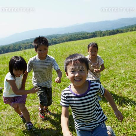 草原を走る4人の子供達の写真素材 [FYI02051168]