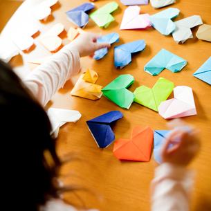折り紙で作ったたくさんのハートと子供の後姿の写真素材 [FYI02051192]