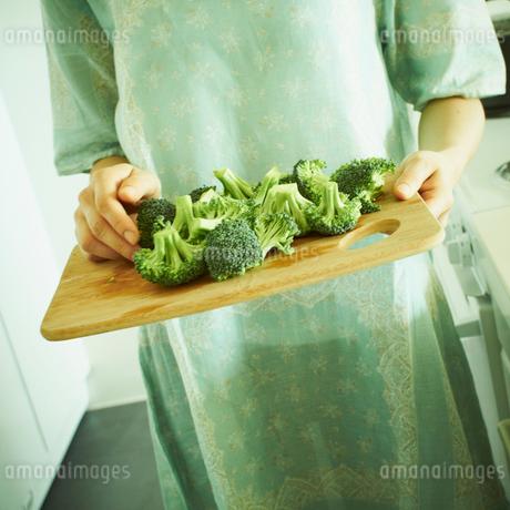 切ったブロッコリーを運ぶ女性の写真素材 [FYI02051195]