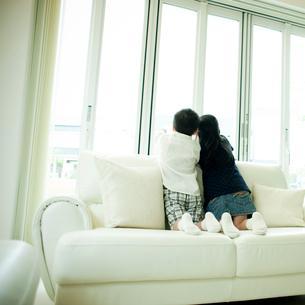 ソファに座り窓の外を眺める男の子と女の子の写真素材 [FYI02051254]