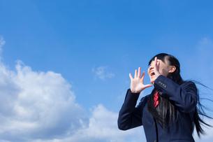 青空と叫ぶ女子学生の写真素材 [FYI02051318]