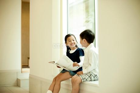 本を持ち窓辺に座る女の子と男の子の写真素材 [FYI02051339]