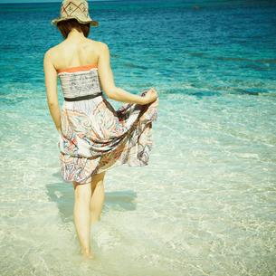 波打ち際で足を浸す女性の写真素材 [FYI02051365]