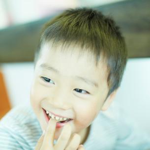 食べ物を口に入れる笑顔の男の子の写真素材 [FYI02051384]