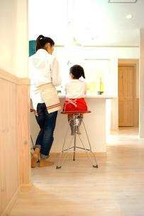 カウンターテーブルの前の母親と娘の写真素材 [FYI02051472]