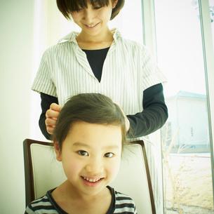 女の子の髪を結う母親の写真素材 [FYI02051491]