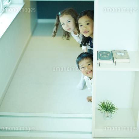 壁から顔を覗かせる子供達の写真素材 [FYI02051549]