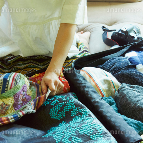 スーツケースに荷物を詰める女性の写真素材 [FYI02051583]
